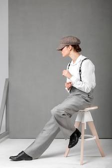 Elegantes weibliches modell, das in einem hocker im eleganten weißen hemd und in den hosenträgern aufwirft. neues weiblichkeitskonzept