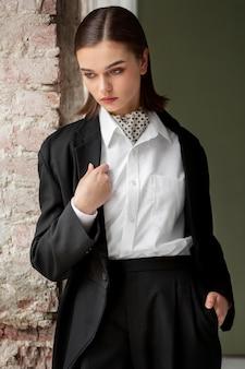 Elegantes weibliches modell, das in einem jackenanzug mit einer krawatte aufwirft. neues weiblichkeitskonzept