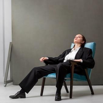 Elegantes weibliches modell, das in einem sessel in einem jackenanzug sitzt. neues weiblichkeitskonzept