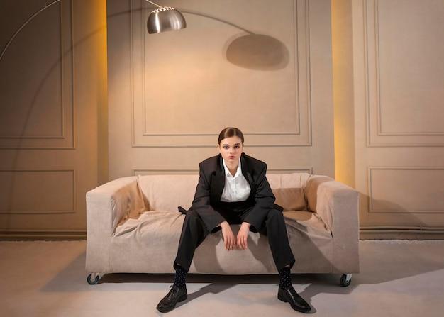 Elegantes weibliches modell, das in einem sofa im jackenanzug aufwirft. neues weiblichkeitskonzept