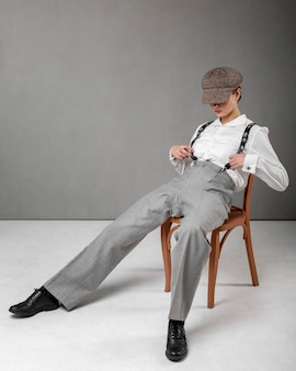 Elegantes weibliches modell, das in einem stuhl im eleganten weißen hemd und in den hosenträgern aufwirft. neues weiblichkeitskonzept