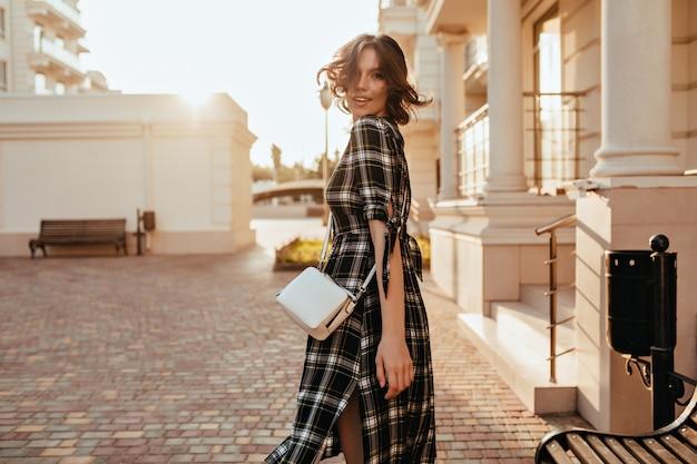 Elegantes weißes mädchen mit der kleinen handtasche, die zurück auf straße schaut. hübsches lockiges weibliches modell im langen kleid, das im herbsttag durch stadt geht.