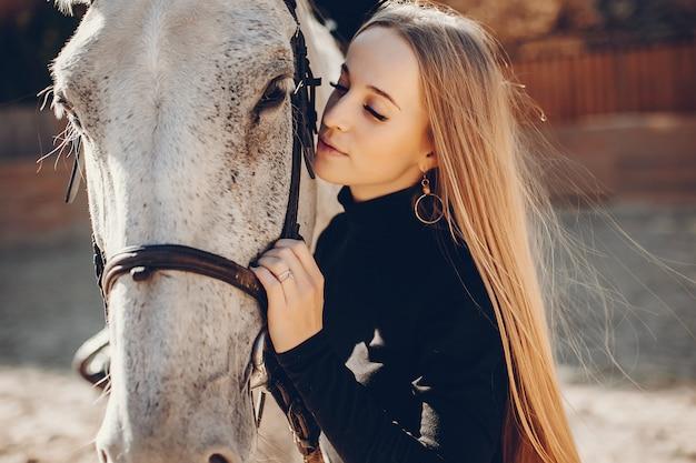 Elegants mädchen mit einem pferd in einer ranch