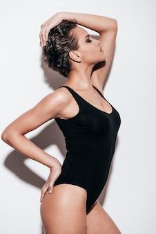 Eleganz und schönheit. seitenansicht einer schönen jungen frau mit kurzen haaren im schwarzen badeanzug, die die augen geschlossen hält, während sie vor weißem hintergrund posiert