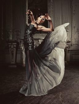 Eleganzfrau mit fliegenkleid im palastraum