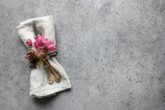 Eleganzfrühlingstischdekoration mit rosa apfelbaumblumen auf grauem hintergrund.