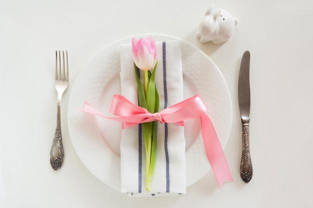 Eleganzgedeck mit rosa band und tulpe auf weißem hintergrund. osterabendessen draufsicht