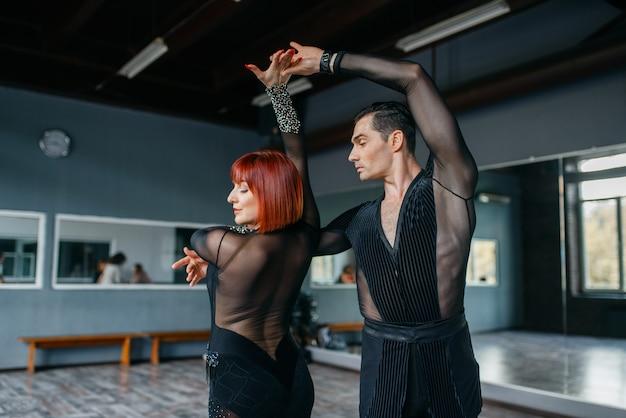 Eleganztänzer in kostümen beim ballrom-tanztraining im unterricht. weibliche und männliche partner beim professionellen paartanzen im studio