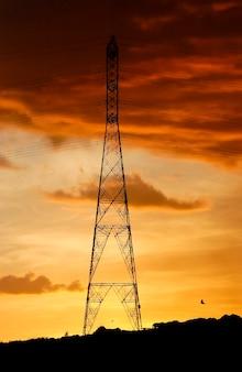 Elektrifizierungsturm mit orangefarbenem himmel am späten nachmittag