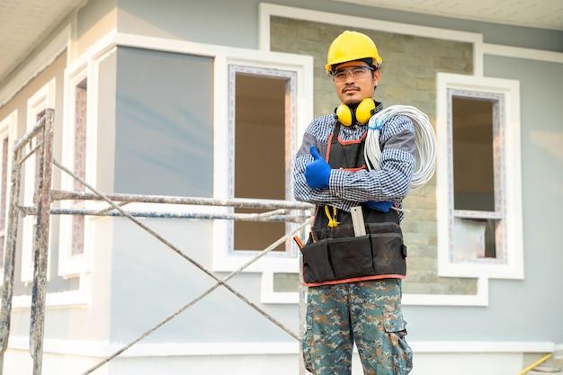 Elektriker arbeitet auf der baustelle, ingenieur, baukonzept.