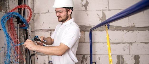 Elektriker arbeitet in der nähe der platine mit drähten. installation und anschluss von elektrik.