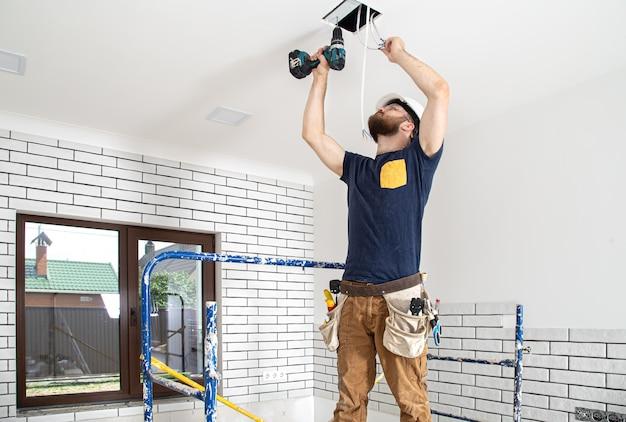 Elektriker builder bei der arbeit, installation von lampen in der höhe. professionell in overalls mit einem bohrer auf der reparaturstelle.