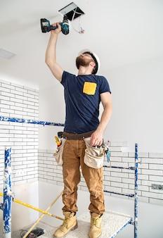 Elektriker builder bei der arbeit, installation von lampen in der höhe. professionell in overalls mit einem bohrer im hintergrund der reparaturstelle.