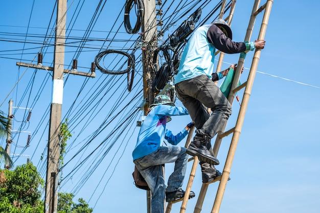 Elektriker, der die bambusleiter klettert, um elektrische drähte zu reparieren.
