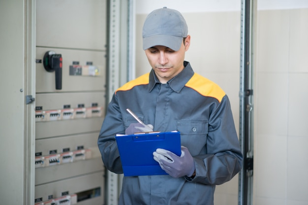 Elektriker, der ein dokument während der inspektion einer platte schreibt