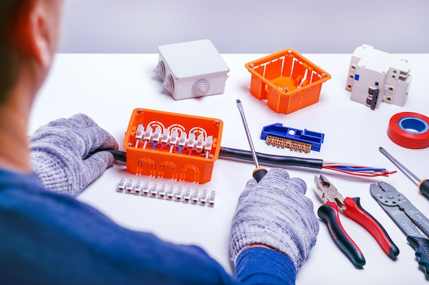 Elektriker, der elektrischen kasten repariert. elektrische geräte reparieren. elektrowerkzeuge und komponenten für die wartung. kleinunternehmen