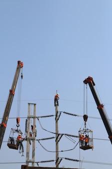 Elektriker, der in der höhe arbeitet, schließen ein hochspannungskabel an