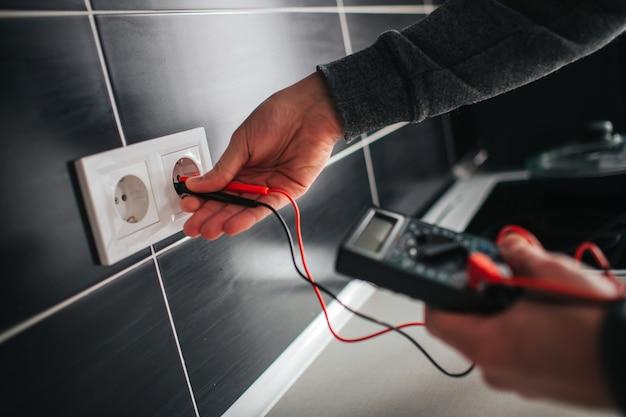 Elektriker, elektriker installiert neue stromsteckdose mit schraubendreher. steckdose oder steckdose installieren - nahaufnahme auf elektrikerhänden.