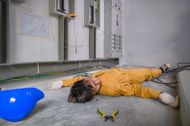 Elektriker erlitt bewusstlos einen stromschlagunfall. elektriker verliert das bewusstsein bei einem stromschlagunfall bei der arbeit vor ort. unfall durch wartungsarbeiten in der werksleitstelle.