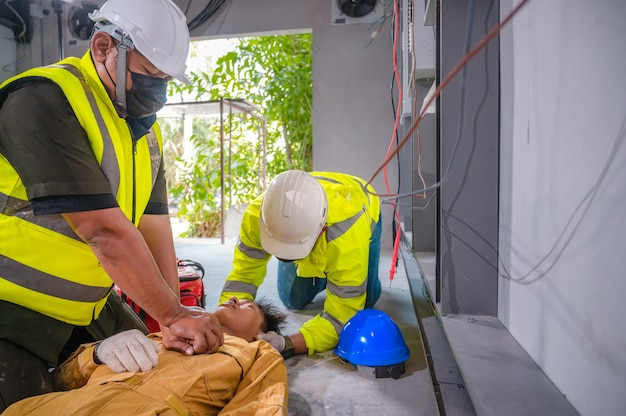 Elektriker erlitt bewusstlos einen stromschlagunfall. sicherheitsteam cpr für erste hilfe elektroarbeiter verliert bei der arbeit vor ort einen stromschlagunfall. unfall im kontrollraum der fabrik.