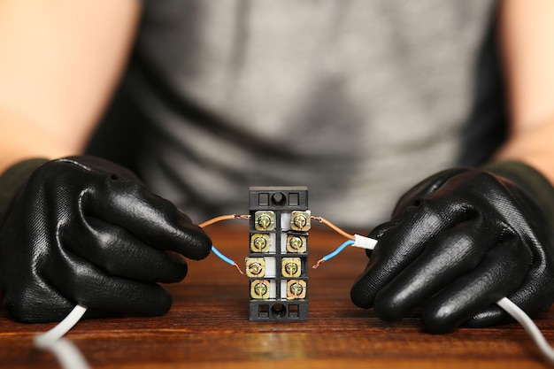 Elektriker hände verbinden drähte in klemmenblock. anschluss von drähten mit klemmen. ein elektriker baut einen stromkreis zusammen. hochwertiges foto