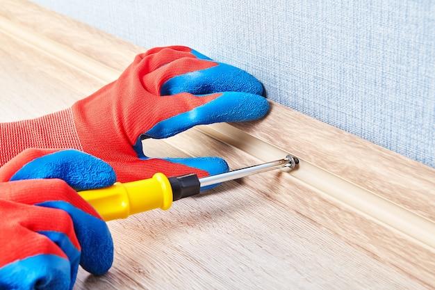 Elektriker in schutzhandschuhen zieht die schraube im kabelkanal des bodensockels fest.