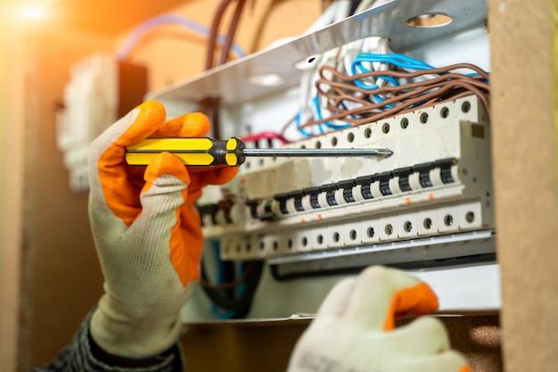 Elektriker installiert steckdose in new house arbeitet elektriker sicher an schaltern und steckdosen eines elektrischen wohnsystems.