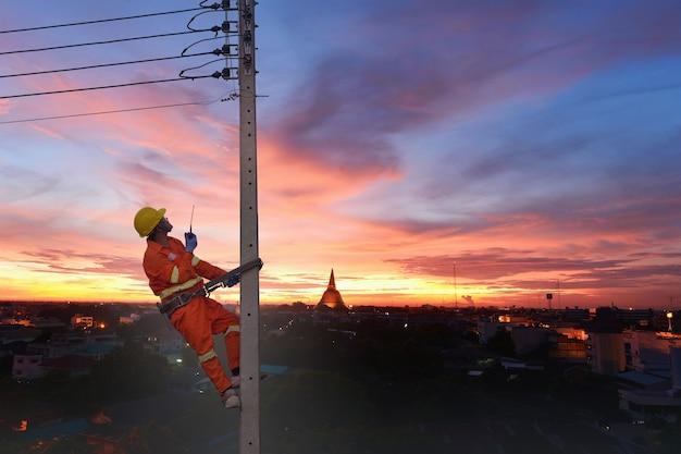 Elektriker klettern auf strommasten, um stromleitungen zu installieren und zu reparierenelektriker arbeiten mit hochspannungsstrom