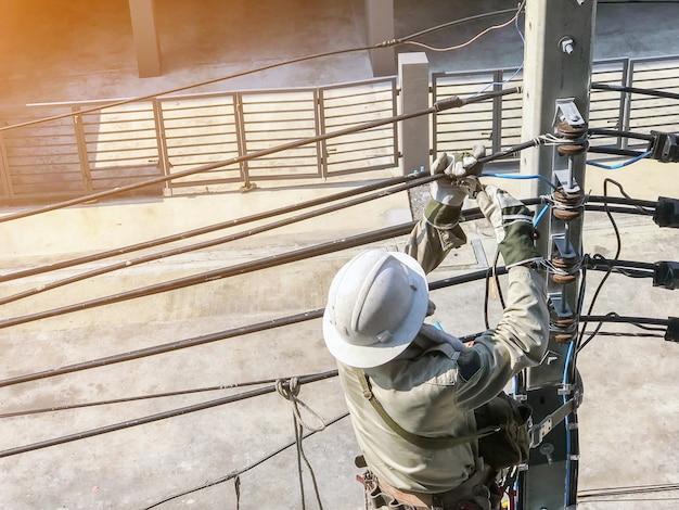 Elektriker klettern auf strommasten, um stromleitungen zu verlegen.