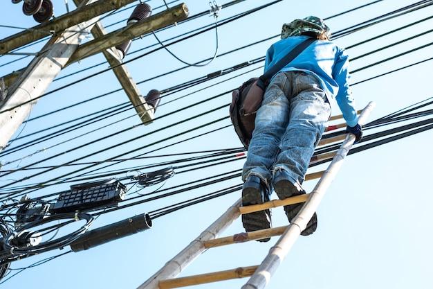 Elektriker klettert die bambusleiter hinauf, um elektrische drähte zu reparieren.