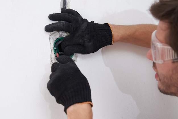Elektriker mann installationsbuchse für die verkabelung in betonwand. renovierungskonzept