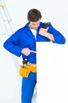 Elektriker mit dem draht, der auf anschlagbrett zeigt