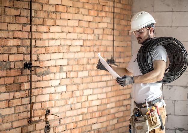 Elektriker mit den bauwerkzeugen, zeichnungen auf der baustelle betrachtend reparatur und heimwerker.