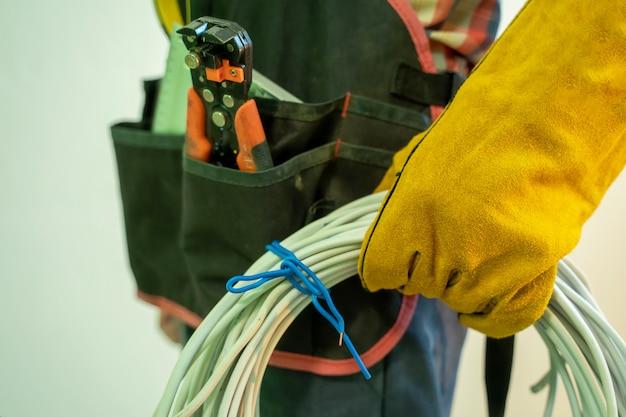 Elektriker mit spezialwerkzeugen, elektriker mit kabelbündel drinnen.