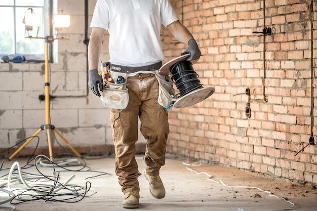 Elektriker mit werkzeugen, auf einer baustelle arbeitend. reparatur- und handwerker-konzept.