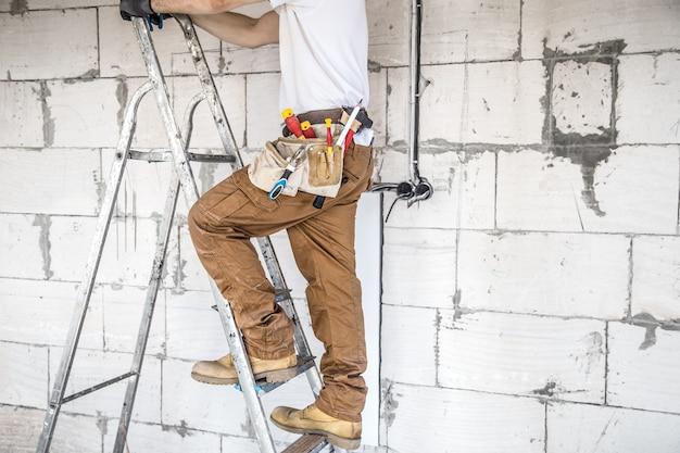 Elektriker mit werkzeugen, auf einer baustelle arbeitend