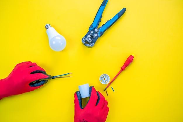 Elektriker schälen isolierung von drähten - nahaufnahme an händen und zangen. selektiver fokus