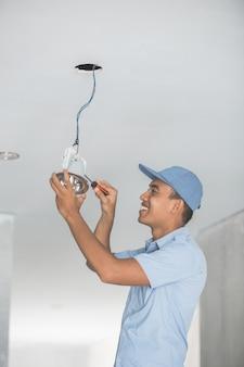Elektriker verkabelt eine deckenleuchte