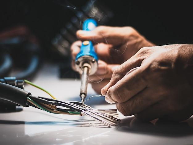 Elektriker verwenden einen lötkolben, um die drähte mit lötkabel an den metallstift anzuschließen.