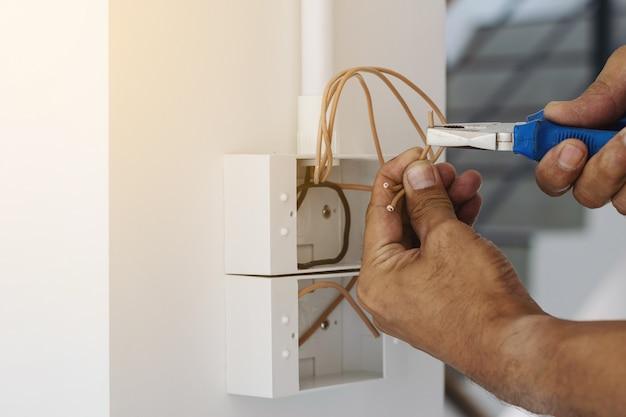Elektriker verwenden einen zangenschlüssel, um den netzstecker an der wand zu installieren.