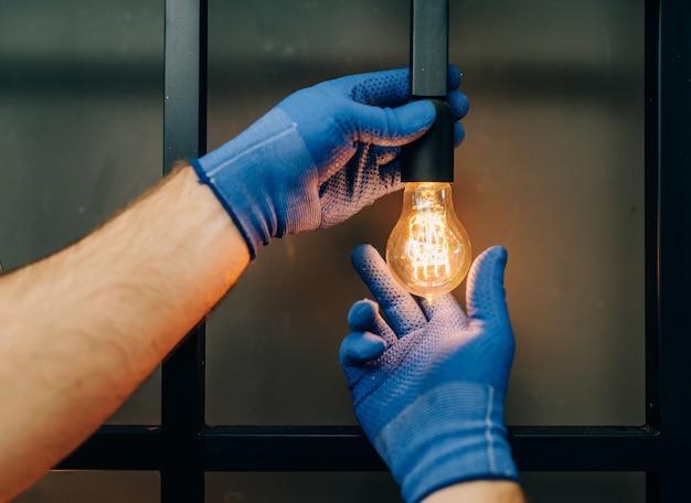 Elektriker wechselt die glühbirne, handwerker