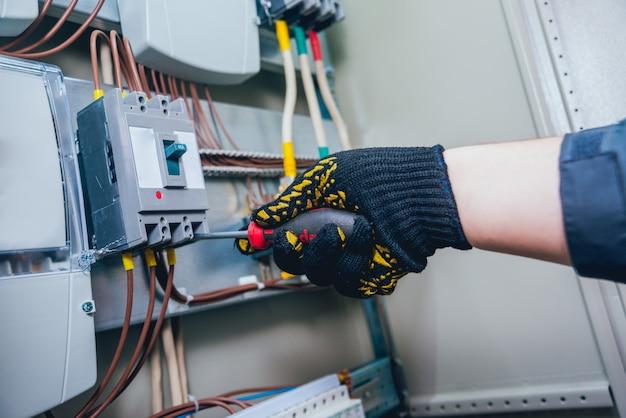 Elektrikerhände, die testschalter in der elektrischen box geprüft werden. schalttafel mit sicherungen