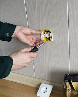 Elektrikerhände installieren eingebaute steckdose in der wand