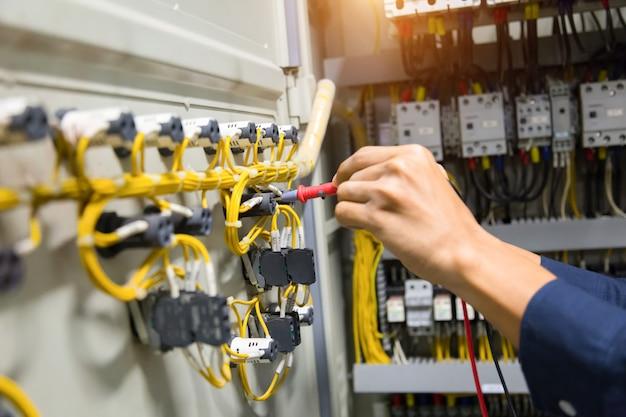 Elektrikerhände prüfen aktuelles elektrisches im bedienfeld.