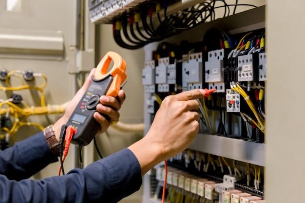 Elektrikeringenieur-arbeitstester, der spannung und strom der stromleitung misst