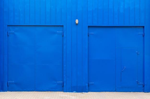 Elektrische blaue wand mit holzbohlen und breiten blauen türen.