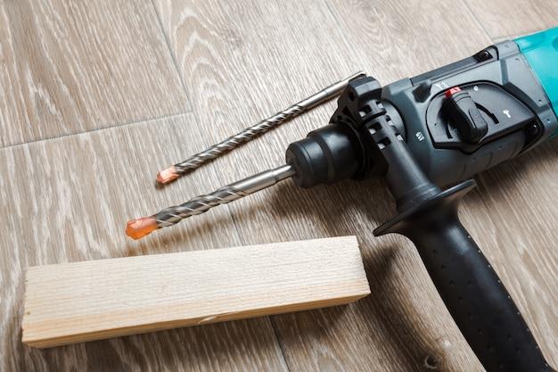 Elektrische bohrhammer liegt auf einem holztisch