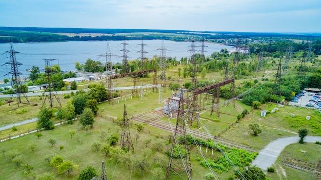 Elektrische fernleitungen über grünen bauernhoffeldern nahe dem fluss. stromleitungen in der wunderschönen landschaft der natur. luftaufnahme