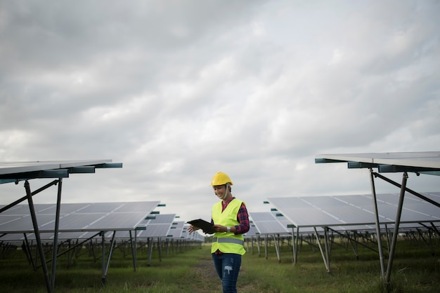 Elektrische frau des ingenieurs, die solarzellen überprüft und wartet.