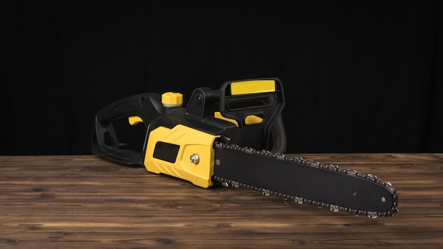 Elektrische kettensäge auf einem braunen holztisch auf einem schwarzen hintergrund. elektrowerkzeug für die holzverarbeitung.